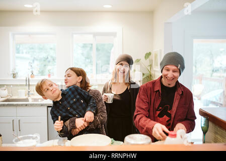 Portrait happy, playful family baking in kitchen - Stock Photo