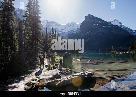 Women hiking along tranquil, idyllic mountain lake - Stock Photo