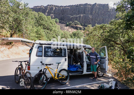 Portrait confident man with mountain bikes at van in remote parking lot, Hood River, Oregon, USA - Stock Photo