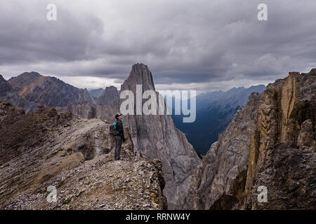 Female hiker at craggy, remote mountaintop, Banff, Alberta, Canada - Stock Photo