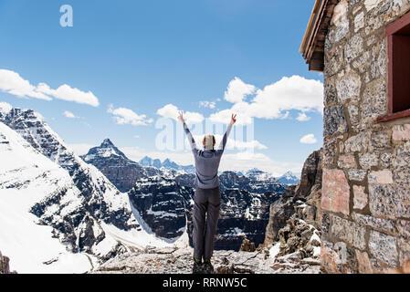 Exuberant female hiker on sunny, snowy mountaintop, Yoho Park, British Columbia, Canada - Stock Photo