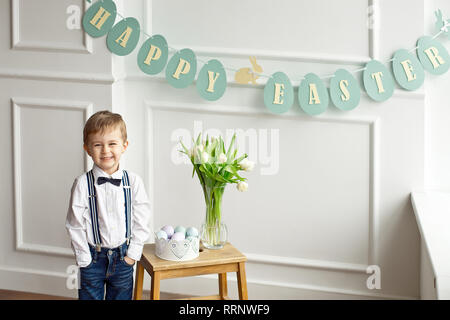 Cute boy in a white shirt and bow tie is standing in a bright room near a wooden table with a glass vase of tulips and a basket of colorful Easter egg - Stock Photo