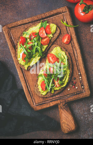 Mashed avocado on rye toast bread served on rustic wooden cutting board. Table top view. Vegan, vegetarian snack or breakfast - Stock Photo