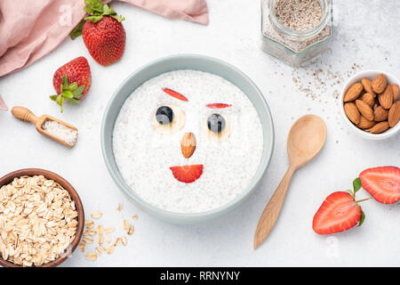 Chia pudding with fruits and nuts for kids. Funny face made with fruits and nuts on yogurt with chia seeds. Breakfast meal for kids - Stock Photo
