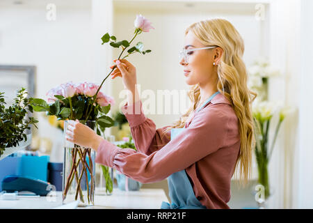 beautiful female florist putting pink rose in bouquet in flower shop - Stock Photo