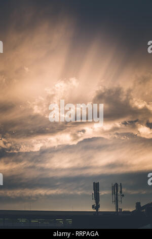 Transmitter antennas in the evening. Orange sky and clouds. - Stock Photo