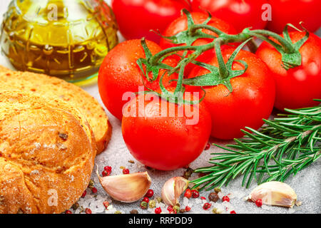 Fresh juicy ripe tomatoes on a branch, red pepper, rosemary, garlic and spices on a gray concrete background. Bread with dried tomato and olive oil. O - Stock Photo