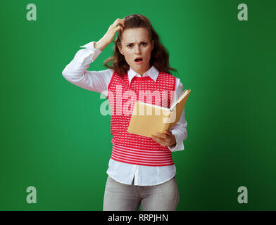 shocked fit student woman in grey jeans and pink sleeveless shirt with a yellow book on green background. - Stock Photo