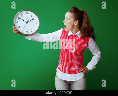 shocked fit learner woman in grey jeans and pink sleeveless shirt looking at white round clock isolated on green. Importance of time management in mod - Stock Photo