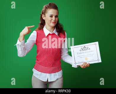 shocked fit learner woman in grey jeans and pink sleeveless shirt with Certificate of Graduation pointing at herself isolated on green background. - Stock Photo