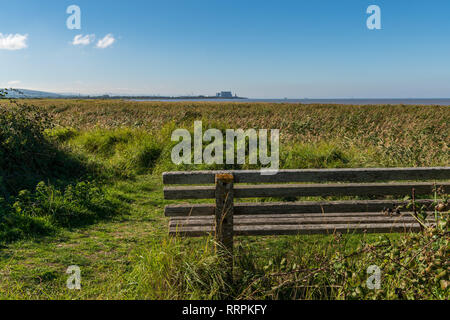 Bridgwater Bay Nature Reserve, England, UK - October 04, 2018: A bench with a view over the Bristol Channel and Hinkley Point Nuclear Power Station in - Stock Photo