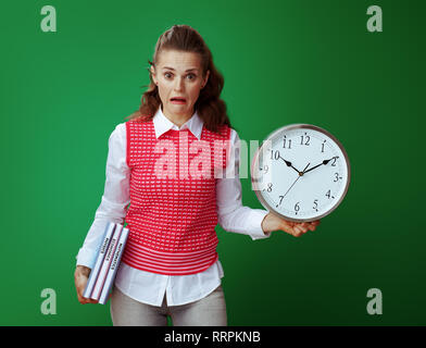 shocked fit learner woman in grey jeans and pink sleeveless shirt with textbooks and white round clock isolated on green background. Importance of tim - Stock Photo