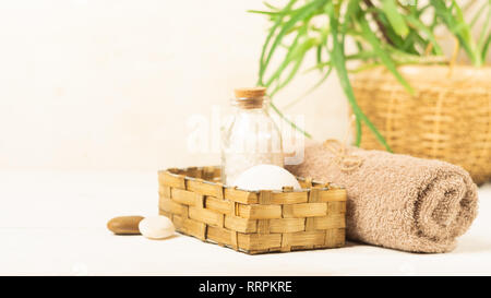 A set of items for the spa procedures. Bath salt, towel, sponge the background o green tropical plant. Beauty concept. - Stock Photo
