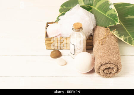 A set of items for the spa procedures. Bath salt, towel, sponge on the background plant. Beauty and body care concept. - Stock Photo