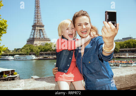 happy young mother and child tourists taking selfie with digital camera against clear view of the Eiffel Tower and river Seine in Paris, France. - Stock Photo