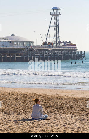Bournemouth, Dorset, UK. 26th Feb, 2019. UK weather: warm weather continues with another lovely warm sunny day at Bournemouth as visitors enjoy the sunshine at the seaside,  expected to be the hottest day of the year and hottest February day ever. Bournemouth beach is voted the best beach in the UK. Young woman sitting on sand looking out to sea. Credit: Carolyn Jenkins/Alamy Live News - Stock Photo