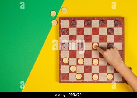 Child hand playing checkers on checker board game over yellow and green background, top view - Stock Photo
