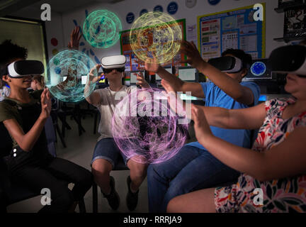 Junior high school students using virtual reality simulators in dark classroom - Stock Photo