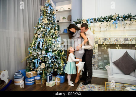 Christmas family standing near the Xmas tree. Living room decorated by Christmas tree and present gift box. - Stock Photo