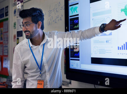 Smiling male teacher leading lesson at touch screen in classroom - Stock Photo