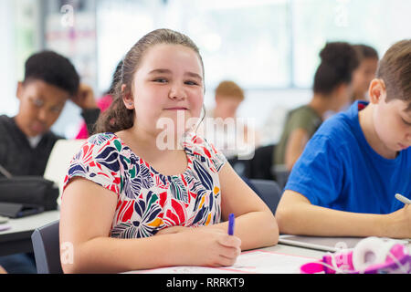 Portrait smiling, confident junior high school girl studying in classroom - Stock Photo