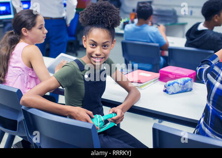 Portrait smiling, confident junior high school girl student with headphones at desk in classroom - Stock Photo