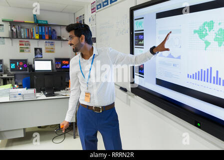 Male teacher leading lesson at screen in classroom - Stock Photo