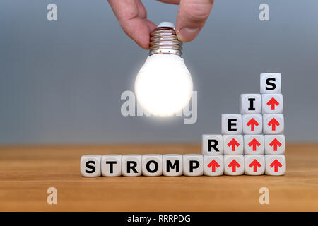 Symbol for increasing electricity rates. Dice form the German word 'Strompreis' ('electricity rate' in English) in front of a light bulb. - Stock Photo