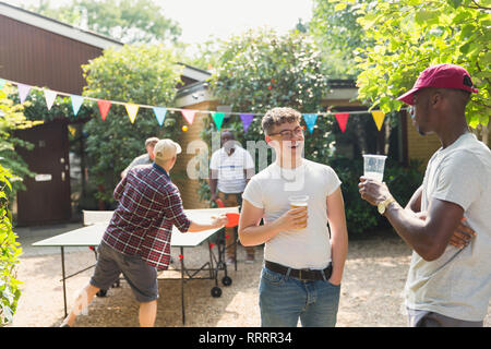 Male friends drinking beer and playing ping pong in summer backyard - Stock Photo
