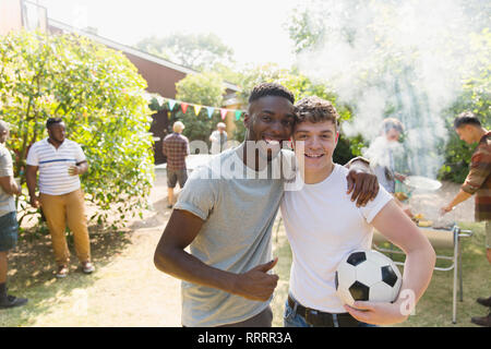 Portrait confident young men with soccer ball enjoying backyard barbecue - Stock Photo