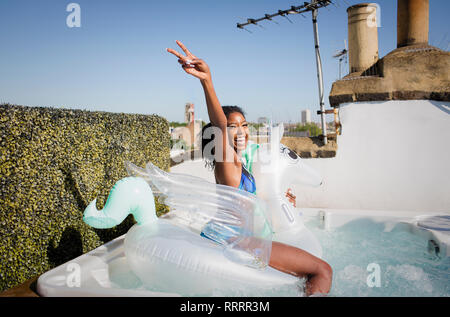 Portrait playful, confident young woman sitting on inflatable pegasus in sunny rooftop hot tub - Stock Photo