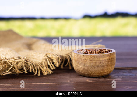 Lot of whole raw red rice jute cloth with wooden bowl with green wheat field in background - Stock Photo