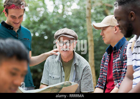 Portrait smiling man with map on hike with friends - Stock Photo