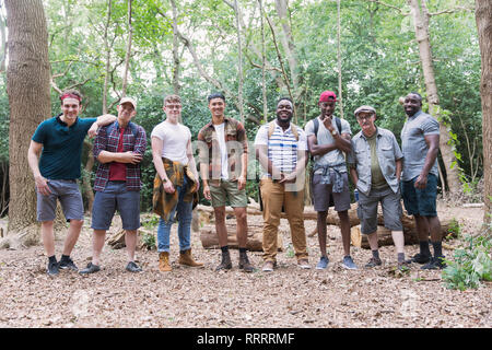 Portrait confident mens group hikers standing in a row in woods - Stock Photo