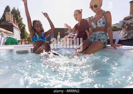 Playful young women friends splashing in sunny hot tub - Stock Photo