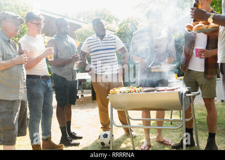 Male friends drinking beer and barbecuing in sunny summer backyard - Stock Photo