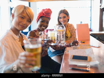 Portrait smiling, confident young women friends toasting cocktails in bar - Stock Photo
