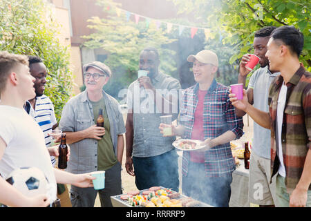 Male friends drinking beer around barbecue grill in backyard - Stock Photo