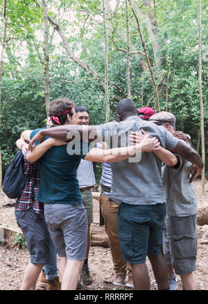 Mens group hugging in huddle, hiking in woods - Stock Photo