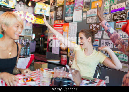 Enthusiastic young women friends cheering in bar - Stock Photo