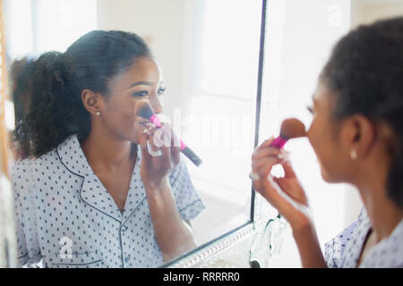 Young woman getting ready, applying makeup in bathroom mirror - Stock Photo