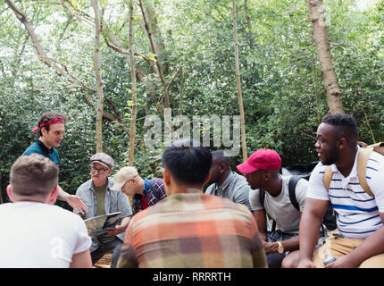 Mens group with map preparing for hike in woods - Stock Photo
