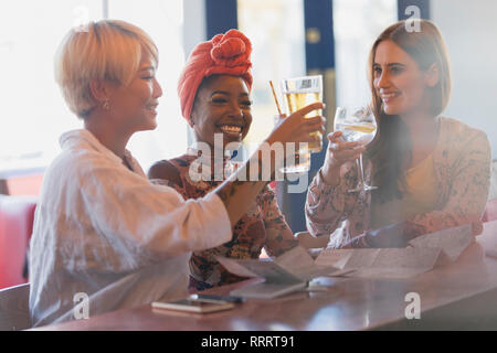 Happy, carefree young women friends toasting cocktail glasses in bar - Stock Photo