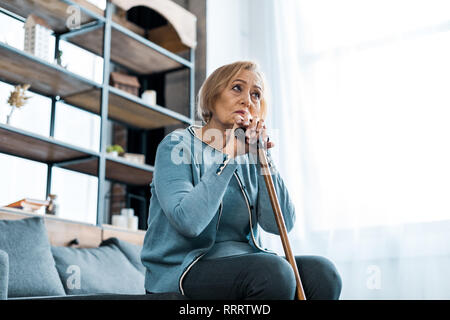 sad senior woman sitting on couch and holding walking stick at home with copy space - Stock Photo