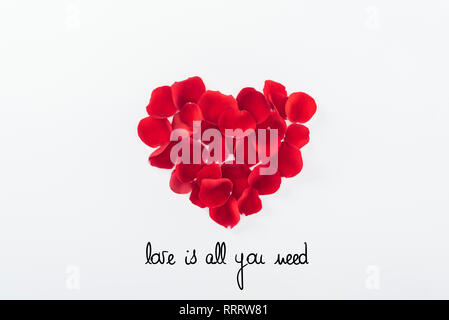 top view of heart made of red rose petals isolated on white, st valentines day concept with 'Love is all you need' lettering - Stock Photo