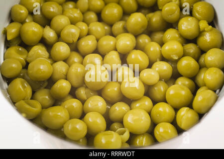 Close-up of green chickpeas in a opened tin can on white background - Stock Photo