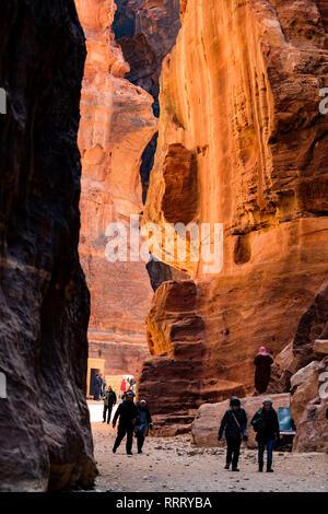 Tourists walk through a huge canyon in the beautiful archaeological site of Petra, Jordan. - Stock Photo