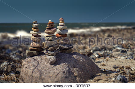 Balanced stone towers in the foreground on the stony beach. In the background the  foam splashes. The sea and the sky meet on the horizon. - Stock Photo