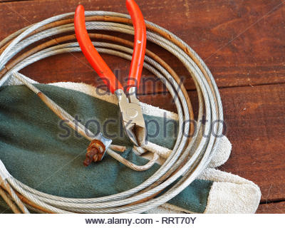 Wire cutters with work gloves and roll of rusty wire on dark wooden background - Stock Photo