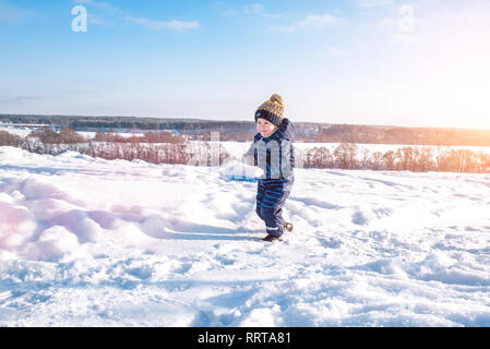 A little boy is carrying snow on a child's shovel. Happy runs in the winter in city park. - Stock Photo